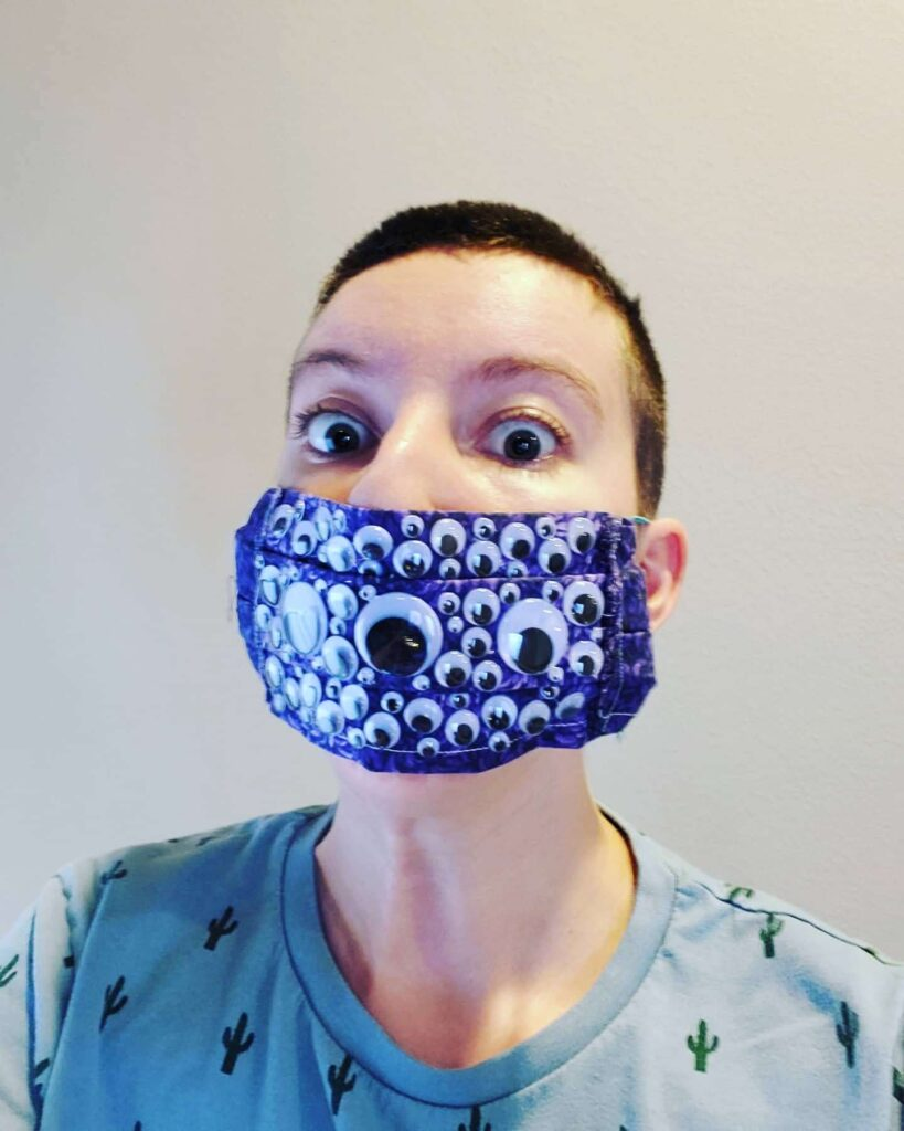 Young woman wearing purple mask with different-sized googly eyes on it.