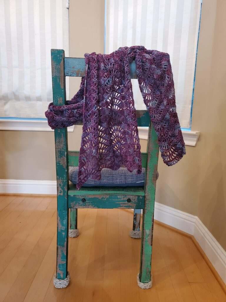 Purple hand knitted scarf draped on back of green chair.